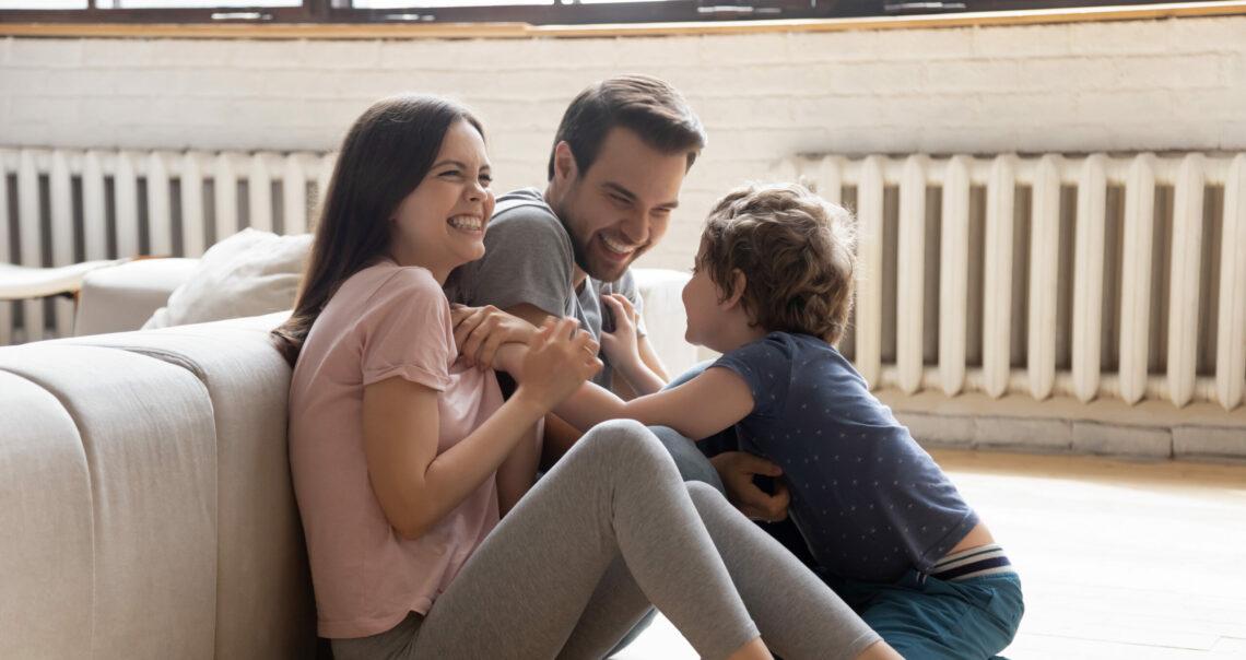 Eine Familie sitzt lachend vor einer Heizung.